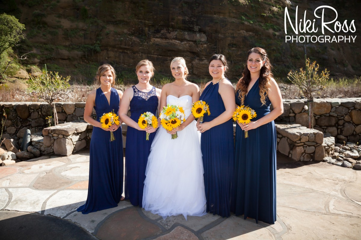 Bridesmaids in long navy blue gowns unique to their style with yellow sunflower bouquets. Blue & Yellow is a gorgeous color pallete for a february wedding at Centerville Estates in Chico, CA - http://nikirossphotography.com