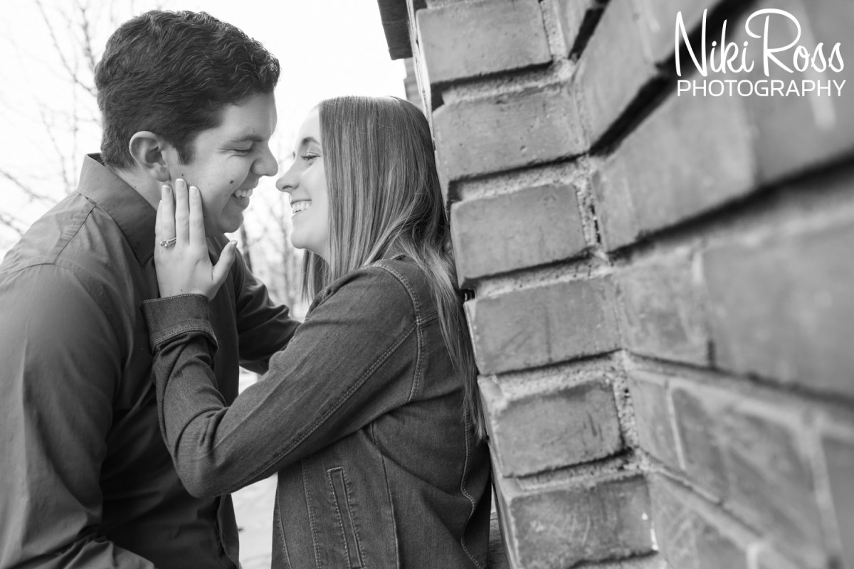 black and white photo of couple leaning against brick wall. Truckee Engagement Session.