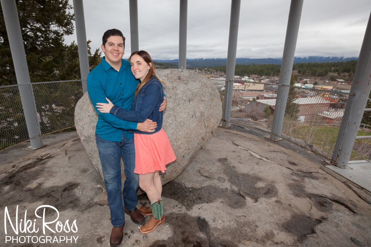 Truckee Engagement Session. Couple leaning against rolling rock which views over downtown Truckee.