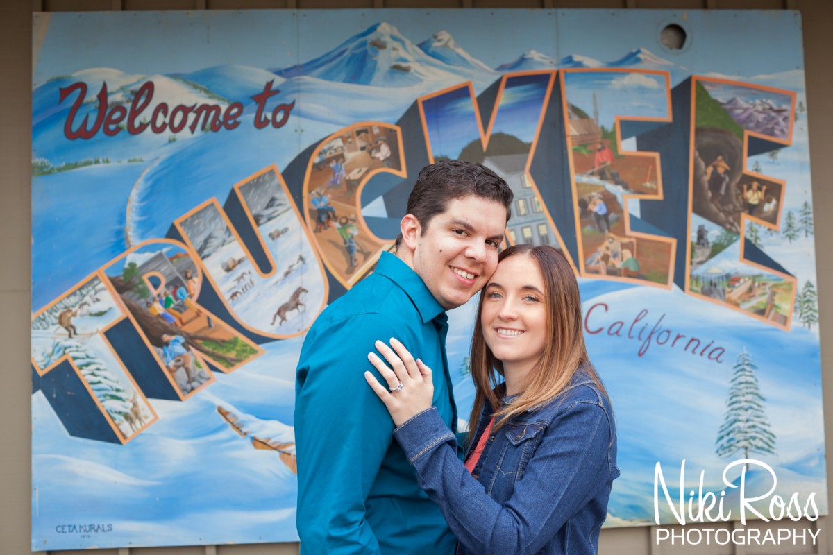 Couple smiling into camera with Welcome to Truckee Sign in the background. Truckee Engagement Session
