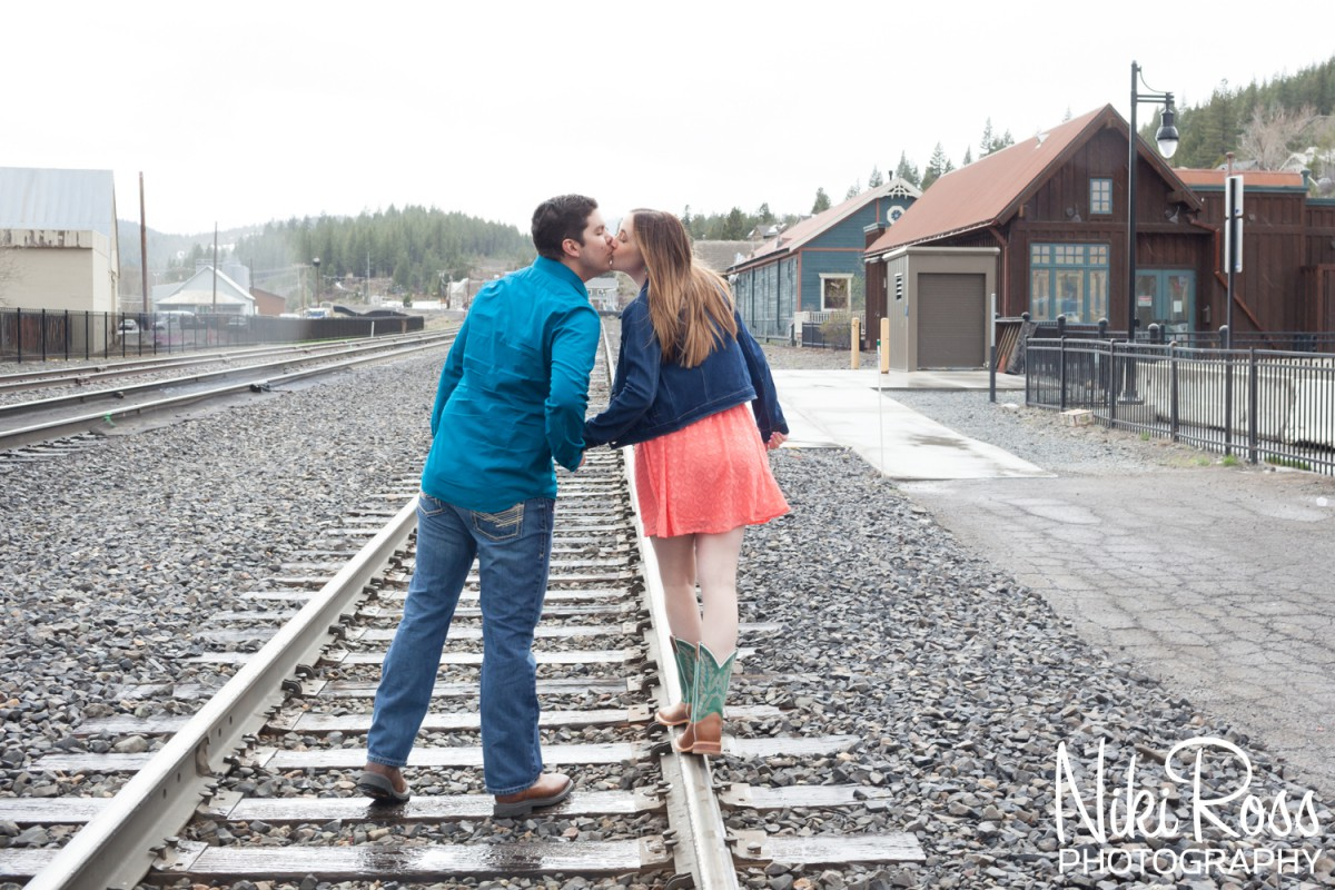 Truckee Engagement Session. Couple walking along the train tracks kissing.